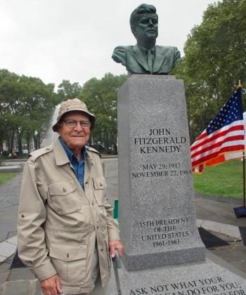 Sculptor Neil Estern poses beside his memorial bust of late President John F. Kennedy at Prospect Park in Brooklyn (Helena Zhu/The Epoch Times)