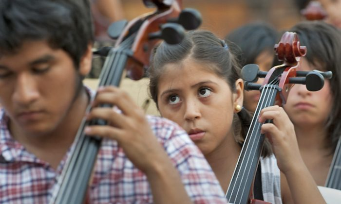 "Children assembled in a school yard play their cellos in Lima, Peru on Feb. 23, 2012, during the string instruments practice, organized by celebrated tenor Juan Diego Florez. Florez was inspired by the 'wonder' Youth Orchestras of Venezuela. Open to anyone between 8 and 16 years with musical interests, the system promotes the creation of ""district clusters,"" where professionals provide free lessons for choral, string, wind and percussion instruments. (Cris Bouroncle/AFP/Getty Images)"