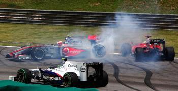 Giancarlo Fisischella drives of course toavoid the spinning Heikki Kovalainen while Kazuki Nakajima passes in the foreground. (Vladimir Rys/Bongarts/Getty Images)