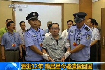 This TV grab, taken on July 23, 2011 from China's Central Television, shows fugitive Chinese businessman Lai Changxing escorted by Chinese authorities after he landed in Beijing aboard a civilian flight in the custody of Canadian police. (STR/AFP/Getty Images)