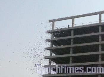 Ten thousand leaflets flutter to the street from a tall building in the Xidan downtown area of Beijing on March 11. (The Epoch Times)