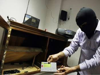 A masked Lebanese secret service officer shows to the media at the Lebanese security services headquarters in Beirut electronic devices found with arrested Lebanese nationals accused of spying for Israel. (Joseph Barrak/AFP/Getty Images)