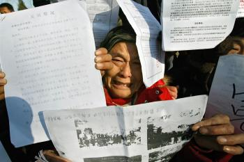 A agitated petitioner shows documents during a gathering in Beijing, 03 December 2007 to protest against corruption and graft ahead of the nation's annual 'legal day'. (Teh Eng Koon/AFP/Getty Images)
