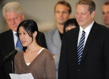 Former US president Bill Clinton (L) and US vice president Al Gore (R) look on as freed US journalist Laura Ling reads a statement at the airport in Burbank, California on August 5, 2009. Following talks in Pyongyang with Clinton, North Korean leader Kim Jong Il pardoned Lee and Ling who were sentenced to hard labor for entering the country illegally. (Robyn Beck/AFP/Getty Images)