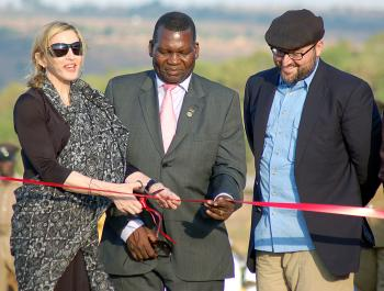 GIVING BACK: (L-R) Madonna cuts a ribbon next to Malawi's Education Minister George Chiponda, and the co-founder of Raising Malawi Girls Academy, Michael Berg during a ceremony to officially launch the construction work of Madonna`s Girls Academy in Lilongwe on October 26, 2009. Madonna broke ground today on a girls` academy she is building in Malawi, billed as a `gift` to the country from where she has adopted two children. (Amos Gumulira/AFP/Getty Images)