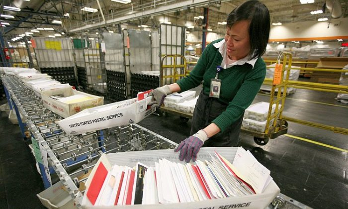 U.S. postal worker Tin Aung moves boxes of letters and cards at the U.S. Post Office sort center in San Francisco, Calif., in 2008. The USPS's most recent consolidation plan begins with closing 48 processing centers this summer. (Justin Sullivan/Getty Images)