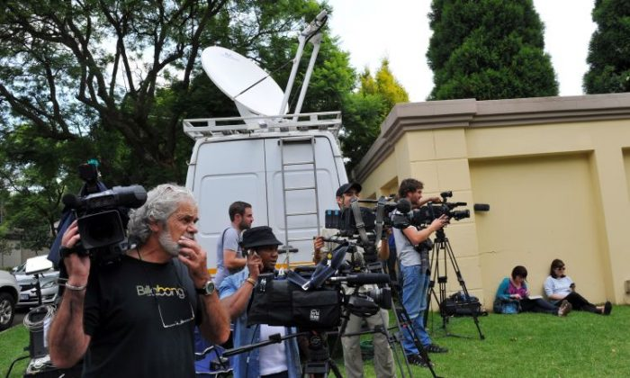 Media stand outside the home of South Africa's former president and Nobel Peace Prize winner in Johannesburg on Feb. 26. Nelson Mandela was discharged from a South African hospital on Sunday after a minor diagnostic procedure. Mandela was admitted on Saturday for an abdominal complaint. (Alexander Joe/AFP/Getty Images)