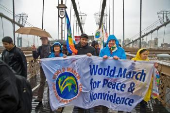 Peace activists march across the Brooklyn Bridge on Monday despite the rainy weather. (Aloysio Santos/The Epoch Times)