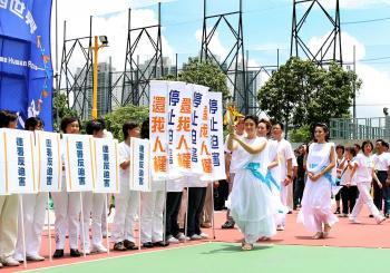 The Goddess of Justice carries the human rights torch past banners calling for a stop to the persecution, and appealing for a return of human rights.  (Li Ming/The Epoch Times)