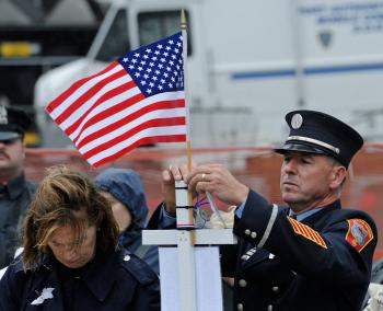 A firefighter posts a small American flag as he pays his respects at Ground Zero during a 9/11 memorial ceremony on September 11, 2009 in New York City. (Peter Foley-Pool/Getty Images)
