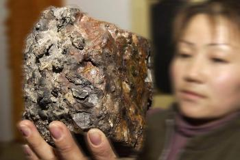 A woman holds up a chunk of meteorite recovered from the hills in China's Gansu province in 2004.
