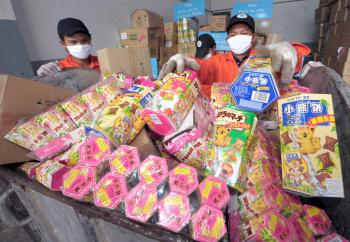 GOT MELAMINE? Thai officials fill snacks and food products tainted with the toxic chemical melamine in a container prior to destruction in Ayutthaya, the capital city of Ayutthaya province on Nov. 10. (Pornchai Kittiwongsakula/AFP/Getty Images)