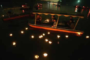 People lay candle lights into a river during the Mid-autumn Festival in Beijing, China. The Mid-Autumn Festival, also known as the Moon Festival, falls on the 15th day of the eighth lunar month. (China Photos/Getty Images)