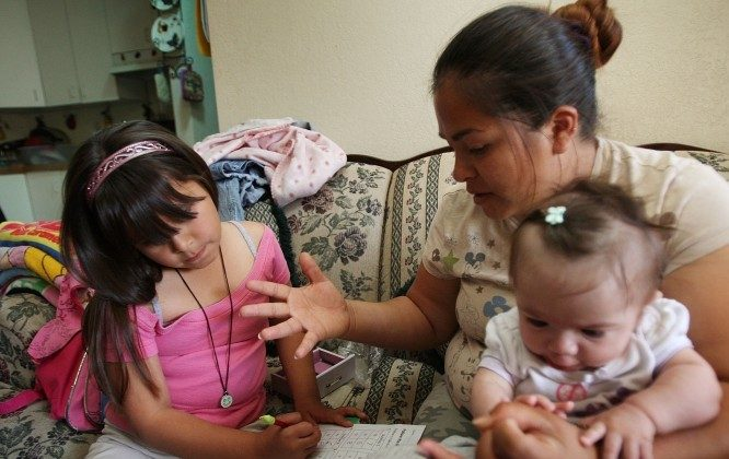 A single, Hispanic mother of five children helps her seven-year-old daughter with homework while holding her five-month-old baby in this file photo. A recent study has shown a significant rise in unwed births since 1970, and deterioration of the American family. (David McNew/Getty Images)