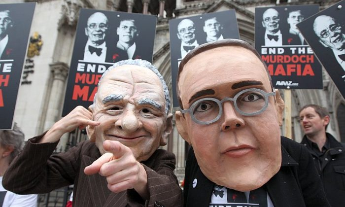 Protesters wearing large Rupert and James Murdoch masks demonstrate outside the High Court in London as former News International Chairman James Murdoch gives evidence to The Leveson Inquiry on April 24. (Oli Scarff/Getty Images)