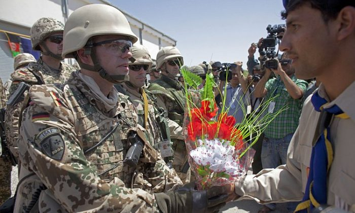 German soldiers of NATO's International Security Assistance Force (ISAF) receive plastic flowers during a security transition ceremony July 23, 2011 in Mazar-e-Sharif, the provincial capital of Balkh province, Afghanistan. (Majid Saeedi/Getty Images)