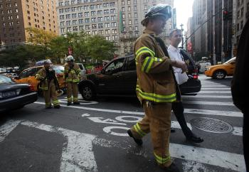 Firefighters walk near the scenes of a PATH commuter train accident Oct. 21, 2009 in New York City. The incident resulted in a few minor injuries. (Mario Tama/Getty Images)
