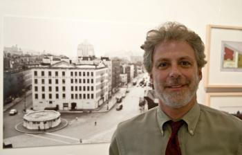 BEFORE THEY WERE PARKS: Curator Jonathan Kuhn stands next to a photo of the Stetler Warehouse, now the site of the Bleeker Street Playground.  (June Kellum/Epoch Times Staff )