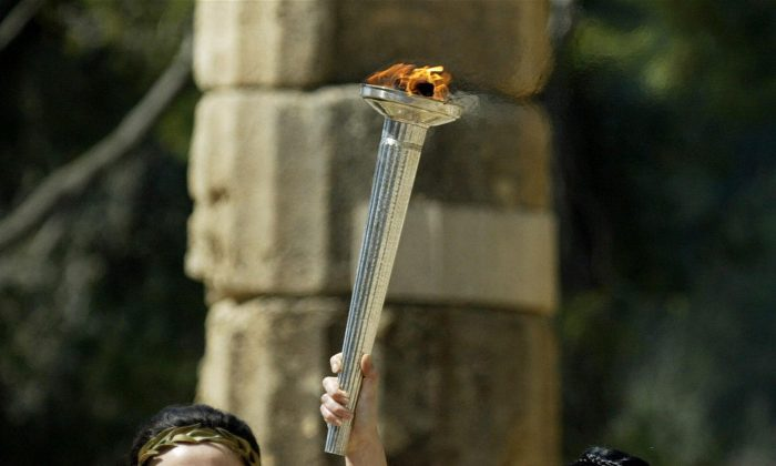 A priestess carries the Olympic Flame to the ancient stadium of Olympia, Greece. The flame, symbolizing the Olympic spirit, will burned at the Athens Games in 2004.   (Aris Messinis/Getty Images)