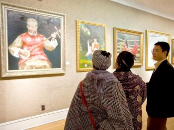 A representative of New Tang Dynasty Television discusses paintings with gallery visitors at the NTD TV Global Chinese Figure Painting Competition exhibition that opened Sunday Nov. 29 at the Salmagundi Club on Fifth Avenue. (Aloysio Santos/The Epoch Times)