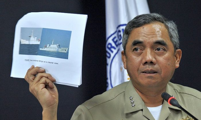 Philippine Navy Vice Adm. Alexander Pama shows a picture of the two Chinese maritime vessels that blocked a Philippine warship from arresting Chinese fishermen on April 11. (Noel Celis/AFP/Getty Images)