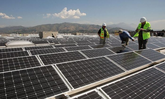 Workers install solar panels on the roof of a Sam's Club store in Glendora, California. (David McNew/Getty Images)