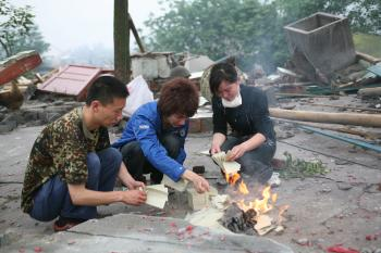 Survivors of the Sichuan earthquake burn paper for their loved ones, a Chinese custom, May 2008. (China Photos/Getty Images)