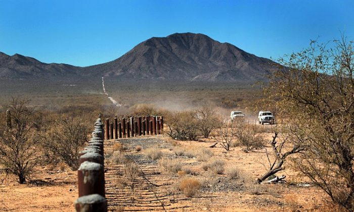 Border Patrol agents drive along the porous U.S.-Mexico border fence, which stretches through the Sonoran Desert in the Tohono O'odham Nation, Ariz., on Jan. 18, 2011. The Native American reservation, which straddles 72 miles of the U.S.-Mexico border, is a key crossing point for narcotics entering the United States. (John Moore/Getty Images)