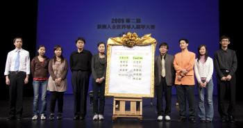 ALL ON STAGE: The nine finalists take a photo with the results board at the end of the semifinal round.  (Edward Dai/The Epoch Times)