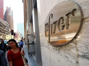 Pedestrians walk by Pfizer Inc.'s world headquarters in New York City. Pfizer is reportedly seeking to buy rival Wyeth to strengthen its business.  (Daniel Barry/Getty Images)