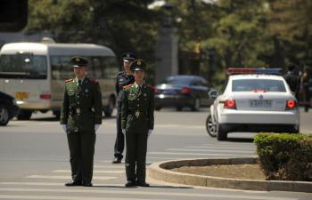Police stand guard as a diplomatic motorcade enters the Diaoyutai State guest house in Beijing on May 6, 2010. North Korean leader, Kim Jong-Il, along with his 17-car luxury motorcade, made his fifth visit to China from May 3 to May 7. (Peter Parks/AFP/Getty Images)