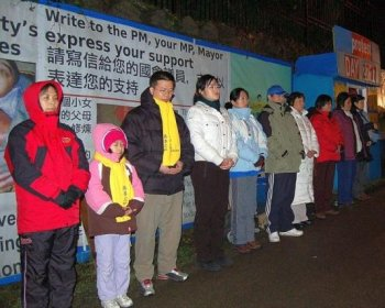 Falun Gong practitioners stand by the blue hut at the protest site the group maintained outside the Chinese consulate on Granville St. from 2001 to 2009. (The Epoch Times)