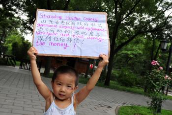 A child displays a placard in a protest park in Beijing which reads 'Shandong Huimin county government illegally sold my grandmother's house and took away the money!' on August 9, 2008. (Frederic J. Brown/AFP/Getty Images)
