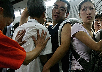 A subway worker (L) pushes commuters into a subway train in Beijing, China, an action that will not go over well with Western tourists next month.  (Guang Niu/Getty Images)