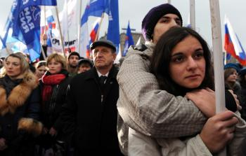 Russians attend an anti-terrorism rally organized by the dominant United Russia political party in memory of those who died in the recent Nevsky Express passenger train tragedy, in Moscow on Dec. 2.  (Alexander Nemenov/AFP/Getty Images)