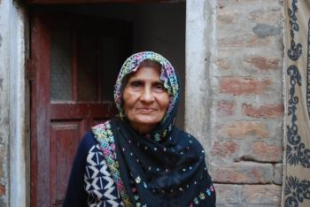 Raizia Beebee, which means respectable lady, stands in front of her home in the town of Chakwal, Pakistan, on March 15. Although she could afford a much more lavish lifestyle and home, she chooses to live simply and spend her money helping others. (Masooma Haq/The Epoch Times)