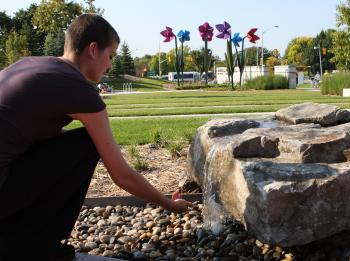 Cancer survivor Rebecca Howe taking a 'hope stone' from The Mary Eagan Garden  (Samira Bouaou/The Epoch Times)