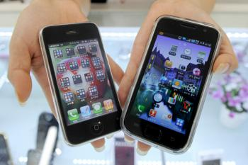 A Samsung Galaxy S mobile phone (R) and an Apple iPhone 3G are shown in a store display. Samsung will add four new cellphones to its galaxy range. (Park Ji-Hwan/AFP/Getty Images)