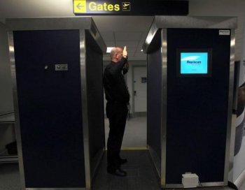 A security officer demonstrates the new full body scanning machine on trial at Manchester Airport on January 7, 2010 in Manchester, England. Last month, ExpressJet pilot Michael Roberts was sent home after refusing the scan and an enhanced pat down.  (Christopher Furlong/Getty Images)