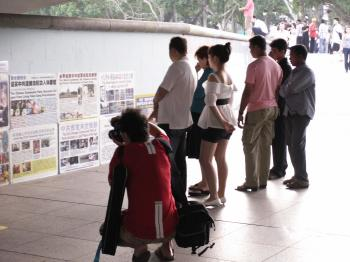 People are reading posters at the walkway below Esplanade Bridge, before police confiscate all posters. (Mingguo Sun/The Epoch Times)