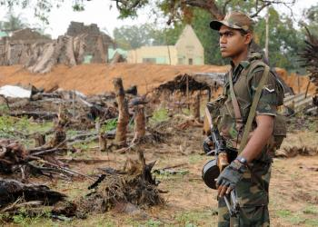 Skeletal remains of civilian houses are seen in the background as a Sri Lankan soldier stand guard inside newly cleared area of Chilawatte on Jan. 27, 2009 in the Mullaittivu district, the former military headquarters of the Tamil Tiger rebels.  (Ishara S. Kodikara/AFP/Getty Images)