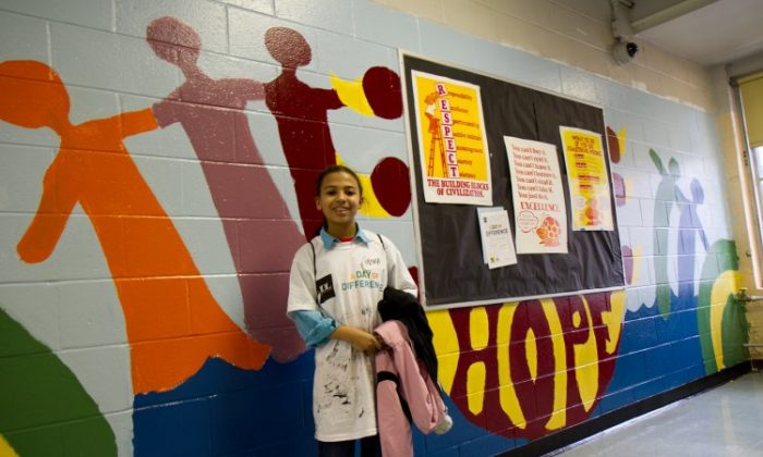 Olivia Logan, a seventh grader at Brooklyn's Math & Science Exploratory School, stands on Sunday in front of a mural she helped create. (Zachary Stieber/The Epoch Times)
