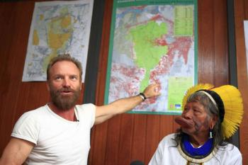 British singer and activist Sting (L) points to a map next to Brazilian indigenous Caiapo chief Raoni during a joint press conference on a hydroelectric power plant construction in Xingu River, in Sao Paulo, Brazil, on Nov. 22, 2009. (Wladimir De Souza/AFP/Getty Images)