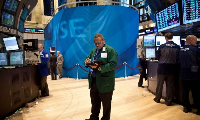 A trader works on the floor of the New York Stock Exchange on March 26. The market soared to a 12-month high after comments made by Ben Bernanke regarding the economy. (Andrew Burton/Getty Images)