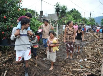 People walk next to the ruins of their homes, destroyed by tropical strom Agatha, on May 30, in the village of Los Almendros, 39 km south of Guatemala City. The first tropical storm of the season has left at least 18 people dead.  (Johan Ordonez/Getty Images)