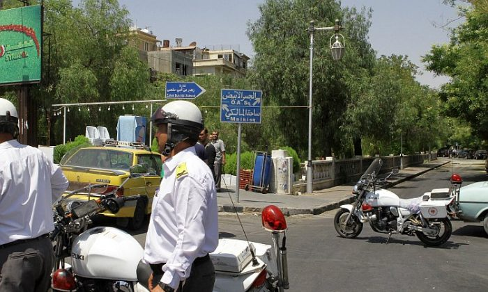 Syrian police guard the road near the scene of the suicide bomb attack that targeted the National Security headquarters in Rawda, a high security district in the heart of the capital, Damascus, on July 18, 2012. (STR/AFP/GettyImages)