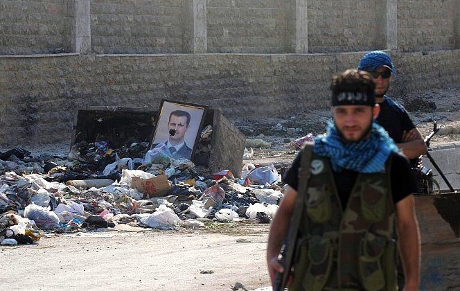 Fighters from the Syrian opposition guard a checkpoint during clashes with forces loyal to President Bashar al-Assad (portrait), in the center of Syria's restive northern city of Aleppo on July 25. (Bulent Kilic/AFP/GettyImages)