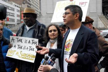 New York Taxi Workers Alliance Committee Member Victor Salazar (R) calls a new tax on cab rides that went into effect on Sunday 'oppression.' (Catherine Yang/The Epoch Times)