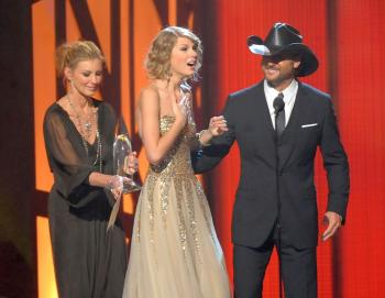 Taylor Swift accepts the award for Entertainer of the Year from singers Faith Hill (L) and Tim McGraw (R) onstage during the 43rd Annual CMA in Nashville, Tennessee. (Rick Diamond/Getty Images)