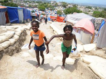 TENT LIFE: Young Haitian girls carry jugs for water at a tent camp near the capital of Port-au-Prince on April 17. Some 230,000 people were killed in the disaster and 1.3 million left homeless. Most now live in makeshift camps, which New York Haitian Consul General Felix Augustin, describes as 'not habitable.' (Thony Belizaire/AFP/Getty Images)